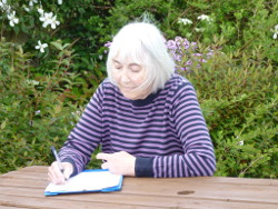 The author writing in her garden.